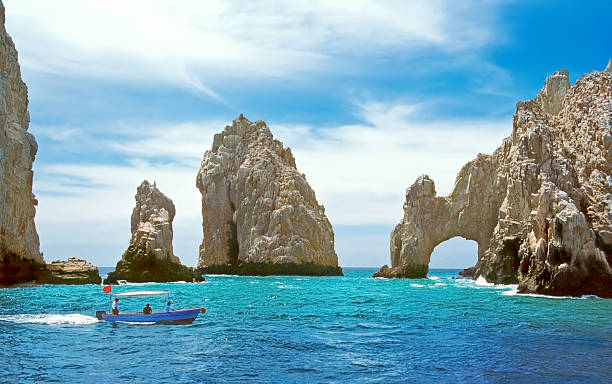 """Land's End & the Arch Closeup Inside the bay at Cabo San Lucas, a small tourboat is dwarfed by rock formations including the famous """"El Arco."""" natural arch stock pictures, royalty-free photos & images"""