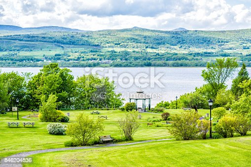 Landscape aerial view of Sainte-Famille park in summer in Ile D'Orleans, Quebec Canada by Saint Lawrence river, village houses, gazebo, picnic tables and path, trail, sky
