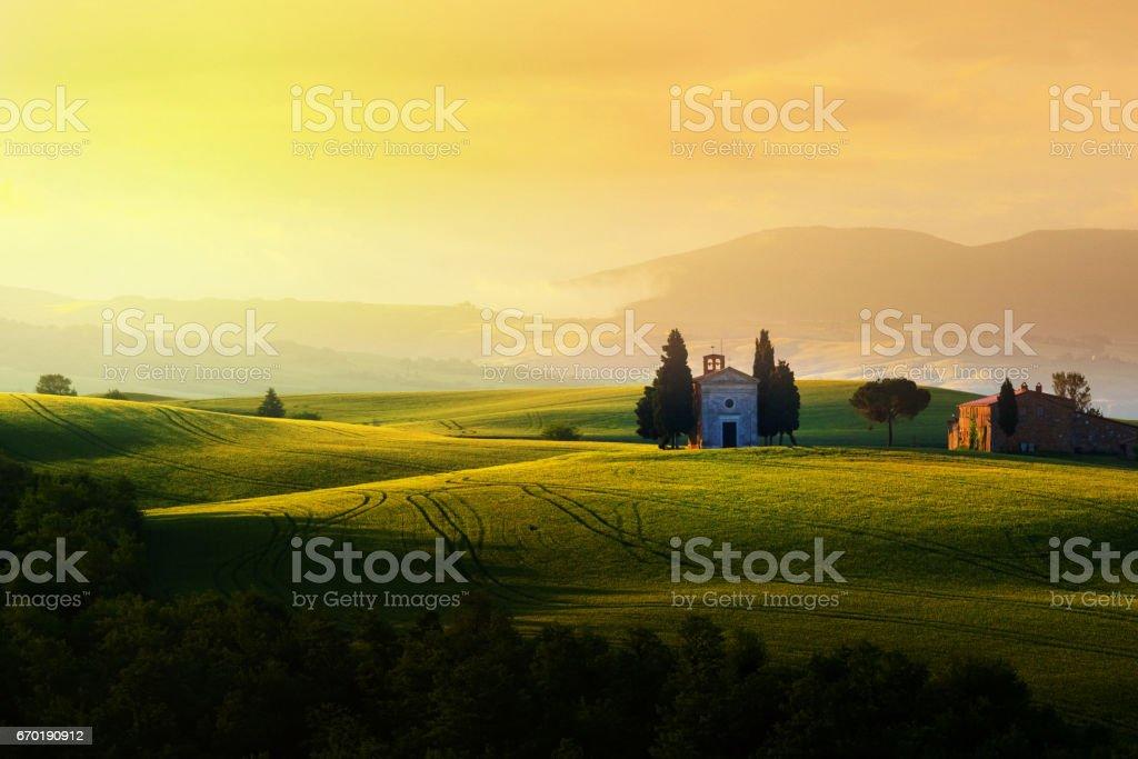 Landscape at sunrise in Tuscany (with the famous Cappella di Vitaleta) stock photo