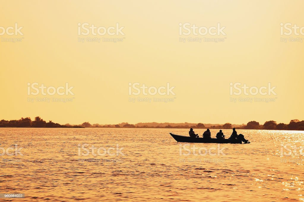 Landscape at sunset of a boat with fishermen fishing on Pantanal stock photo