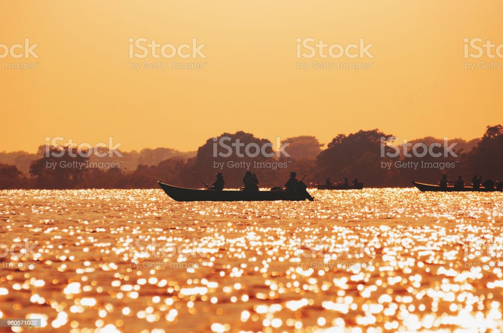 Landscape at sunset of boats with fishermen fishing on Pantanal stock photo