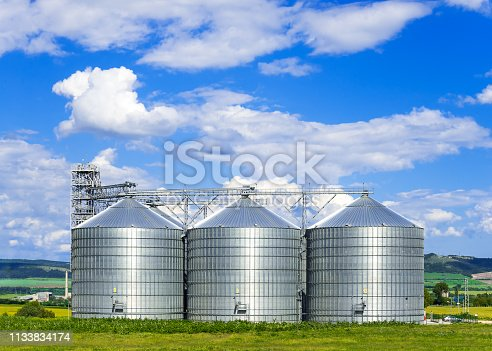 Landscape. Bright nature. Elevator. Large Aluminum containers for storing cereals in the background of blue sky and volumetric clouds