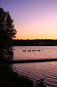 Sunset on a lake with small boats with masts without sails.