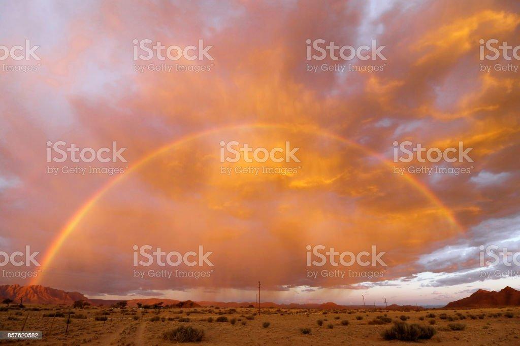 Landscape cloudscape rainbow sky colorful desert Namibia Africa rain...