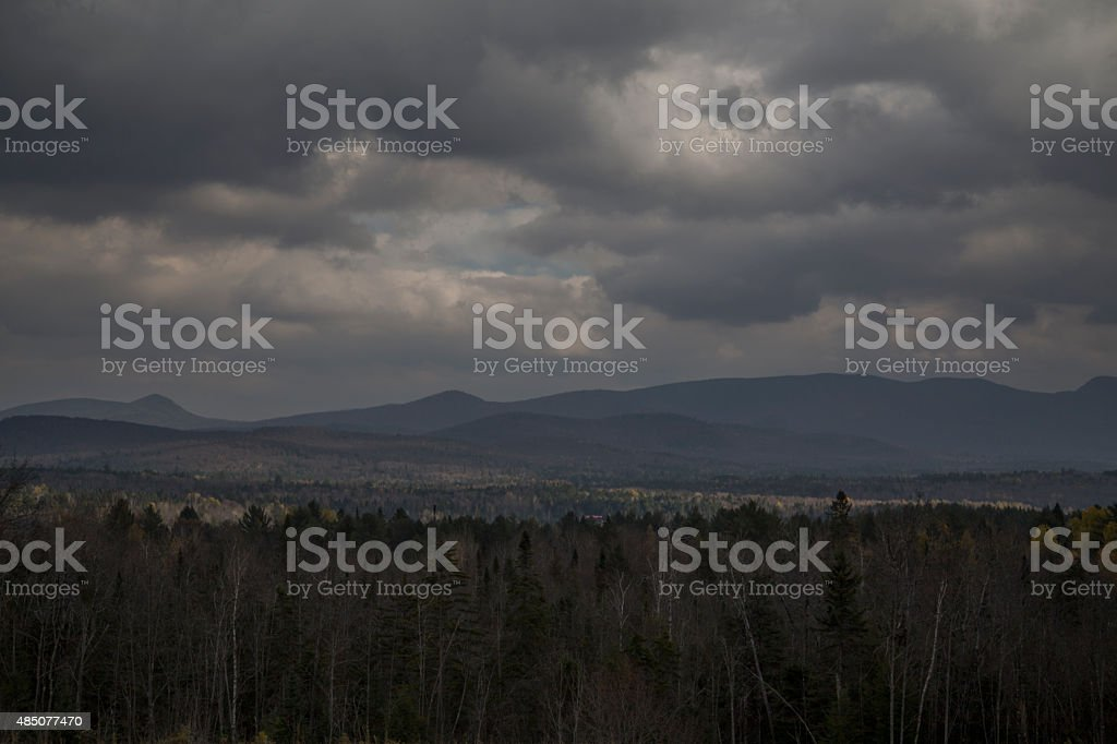 Dark storm weather over rural area with forest, mountain and cumulus...