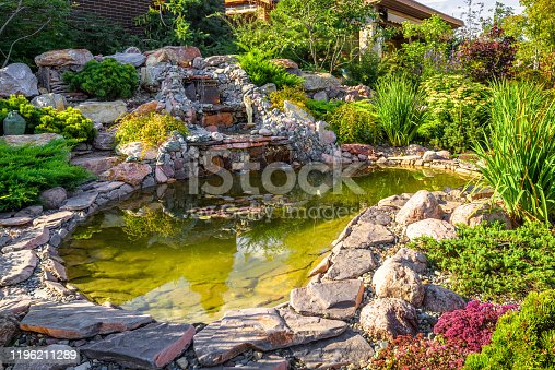 Landscape design of home garden close-up. Beautiful landscaping with small pond and waterfall. Landscaped place with rocks at country house. Stone landscaping in luxury backyard or yard in summer.