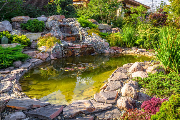 Landscape design of home garden close-up. Beautiful landscaping with small pond and waterfall. Landscape design of home garden close-up. Beautiful landscaping with small pond and waterfall. Landscaped place with rocks at country house. Stone landscaping in luxury backyard or yard in summer. pond stock pictures, royalty-free photos & images