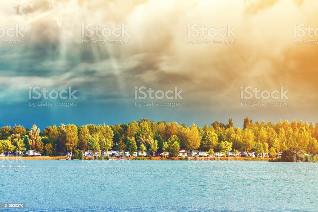 Landscape distant horizon view of riverbank grass beach with many trees and camping site in background for tourists during overcast weather stock photo