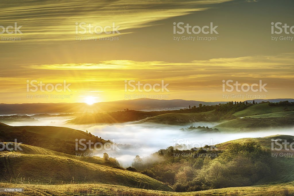 Landscape - Fog in the valleys of Tuscany at dawn stock photo
