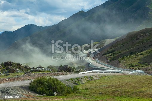 Landscape in the mountains of Altai, disturbed by two large trucks filled with rubble, rising up for the hill, a large amount of dirty dust flies and during construction of road in hard-to-reach place