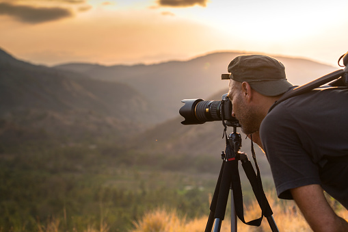 A matured man photographer is looking through the viewfinder and takes photographs of hills and mountains at sunset time, with a tele photo lens mounted on tripod.