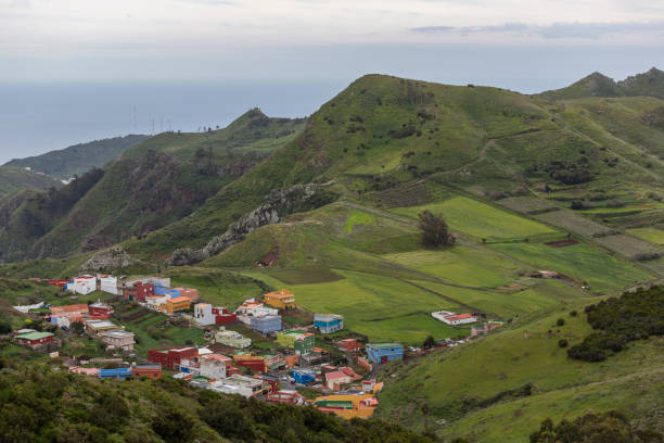 Landscape of a colorful town seen from a viewpoint in the mountain with green hills in Tenerife stock photo