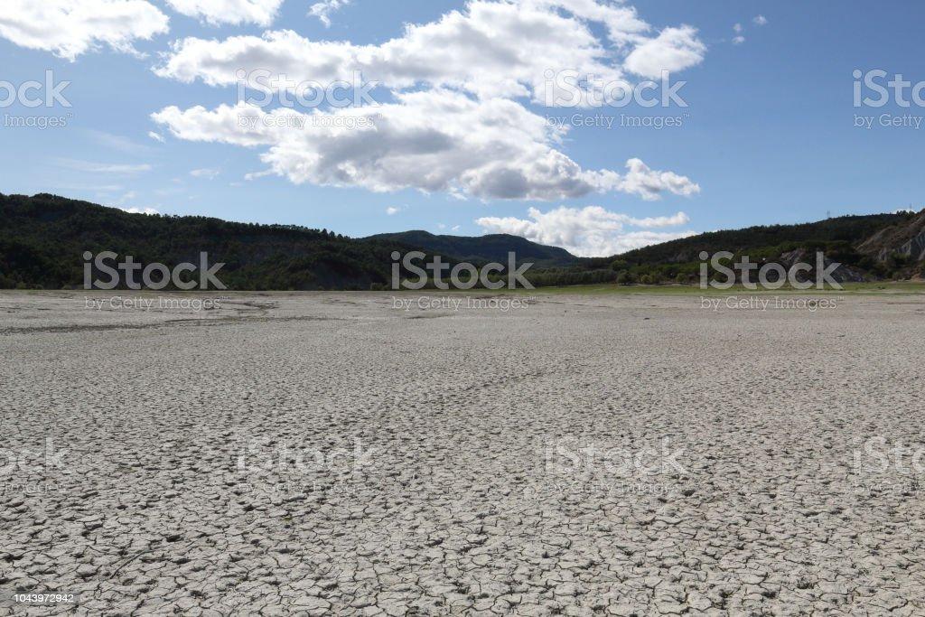 Un paisaje de un suelo de arcilla gris agrietado seco durante un día asoleado caliente, con montañas al fondo, en el lago artificial del Mediano en el Pirineo Aragonés Español - foto de stock