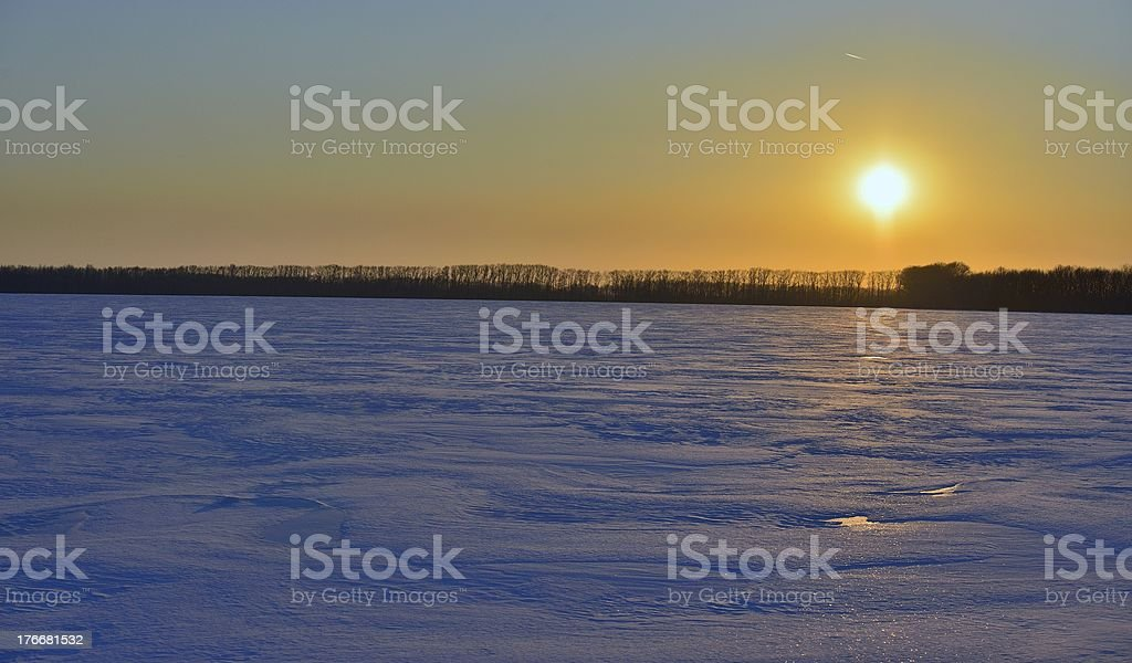 Landscape of a snow-covered field and sunset royalty-free stock photo