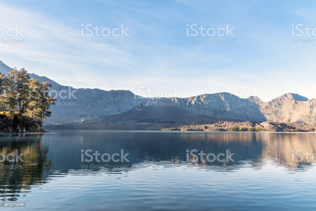 landscape of active volcano Baru Jari, Lake Segara Anak and summit of Rinjani mountain. Lombok island, Indonesia. stock photo