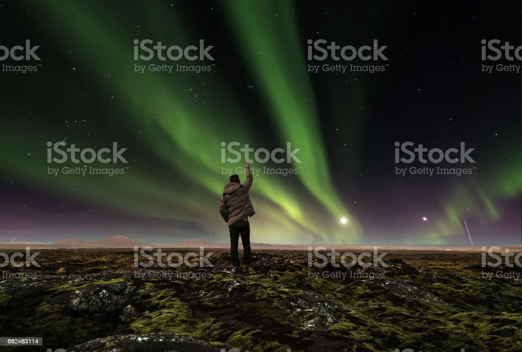 landscape of amazing beautiful  natural phenomenon Aurora Borealis, with a man raising arm , traveling in Iceland stock photo