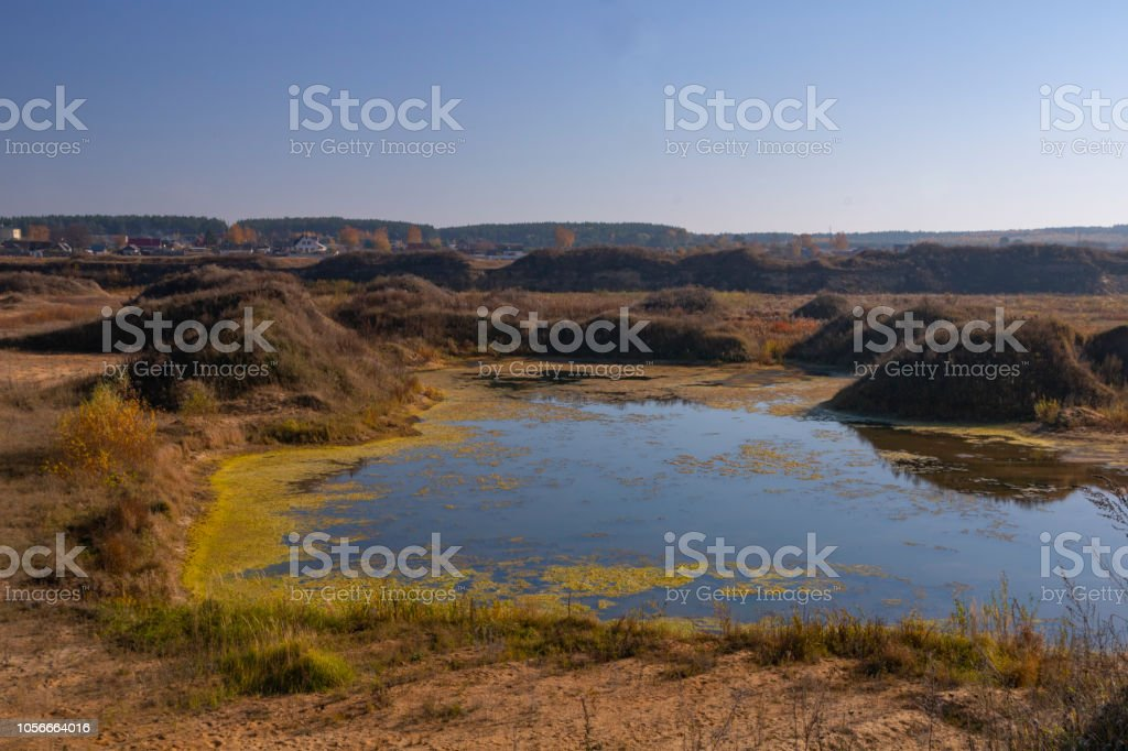 Landscape of an old flooded industrial granite quarry filled with water. Lake on the background of rocks and fir trees. Canyon. The nature of autumn. Place for text and design. stock photo