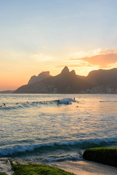 Landscape of Arpoador bech in Ipanema with hills and surfers stock photo