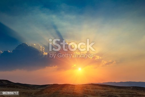 Landscape of beautiful sunset in the desert. View of  high sandstone hills and  dramatic cloudy sky. Sinai Peninsula.