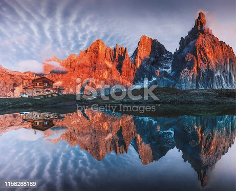 Landscape of beautiful sunrise view with red sunlights on mountains and beautiful clouds from the north western face of the Pale di San Martino, on the left   Baita Refuge in Trentino Alto Adige, Dolomiti, Italia.
