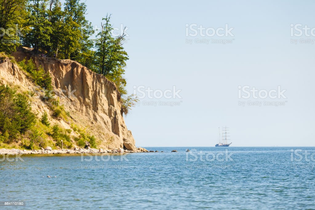 Landscape of cliff near sea and ship on water royalty-free stock photo