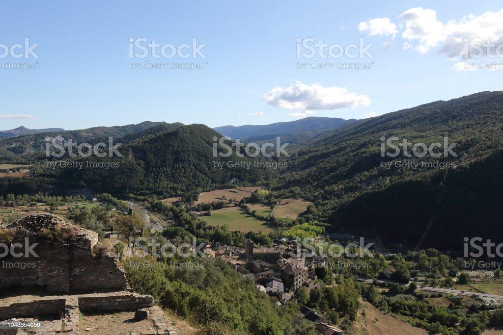 Un paisaje de campos cultivados, densos bosques y montañas como se ve en las ruinas del castillo abandonado en el rural pueblo medieval de Boltaña, en el Pirineo Aragonés Español - foto de stock