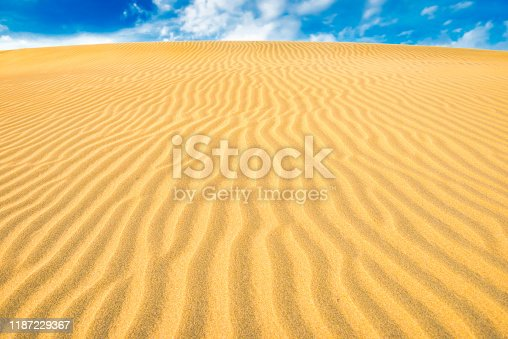 Landscape of desert sand dunes and blue sky with clouds over them