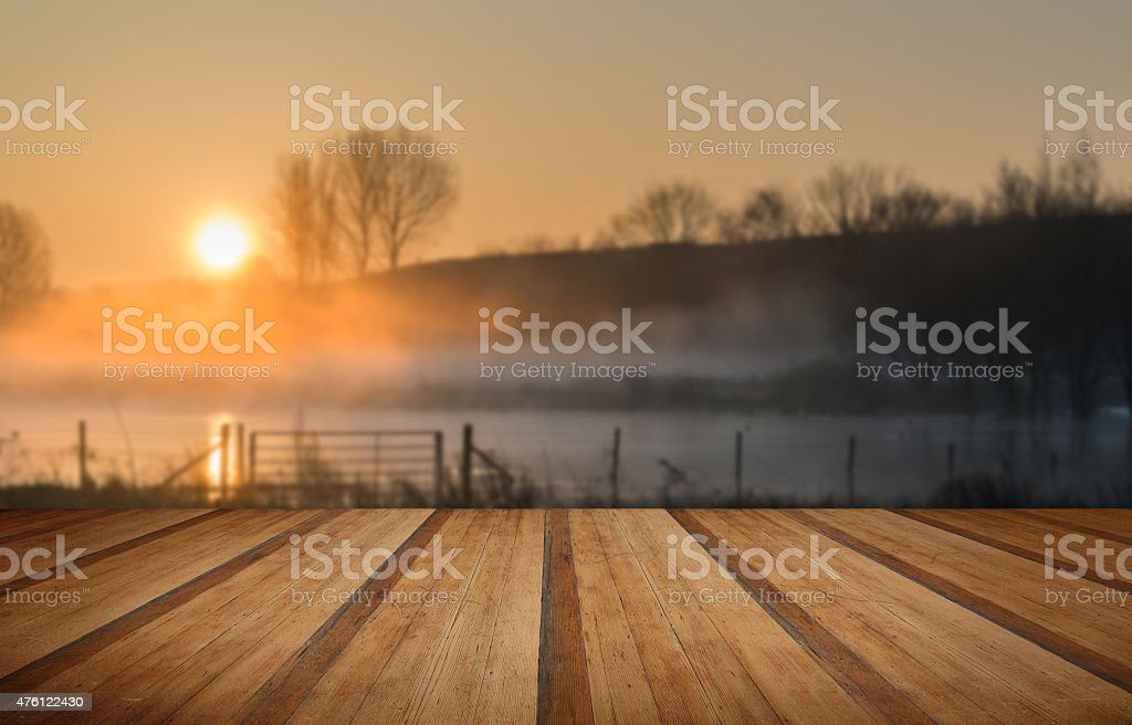 Landscape of lake in mist with sun glow at sunrise stock photo