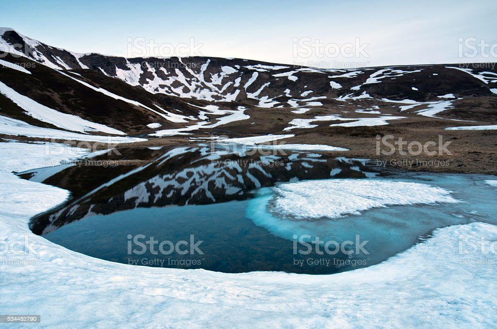 Landscape of lake with transparent water, ice bottom and distant stock photo