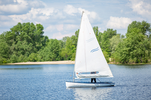 Landscape of lake with white yacht on bright sunny summer day. Blue sky with white clouds over big lakes and green trees and hills on horizon.