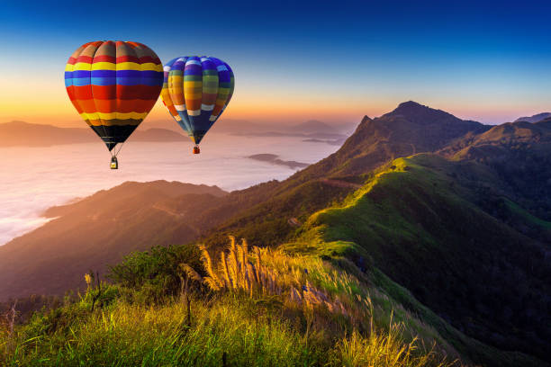 Landscape of morning fog and mountains with hot air balloons at sunrise. stock photo