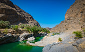 Oman landscape with mountains, green water and blue sky.