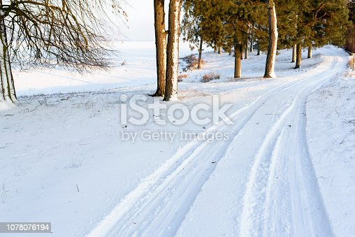 Picturesque view on road in the forest covered by snow. Car traces in deep snow. White winter.