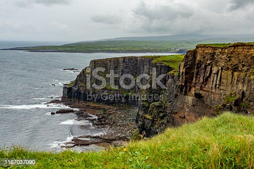 Landscape of rocky cliffs along the coastal walk route from Doolin to the Cliffs of Moher, geosites and geopark, Wild Atlantic Way, spring rainy day in the countryside in county Clare in Ireland
