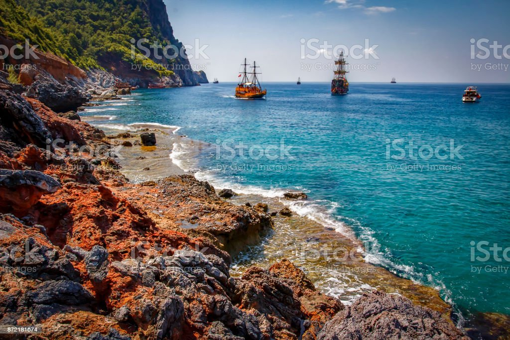 Landscape of rocky turkish beach with ships on horizon in Alanya. Scenery sea and mountains in sunny summer day at Turkey. Coastline in tropical paradise bay stock photo