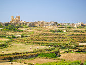 Rural Gozo landscape with small village on top of hill, from fortified city Cittadella wall.