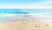 Landscape of sea sky and sand beach with footprints in summer day