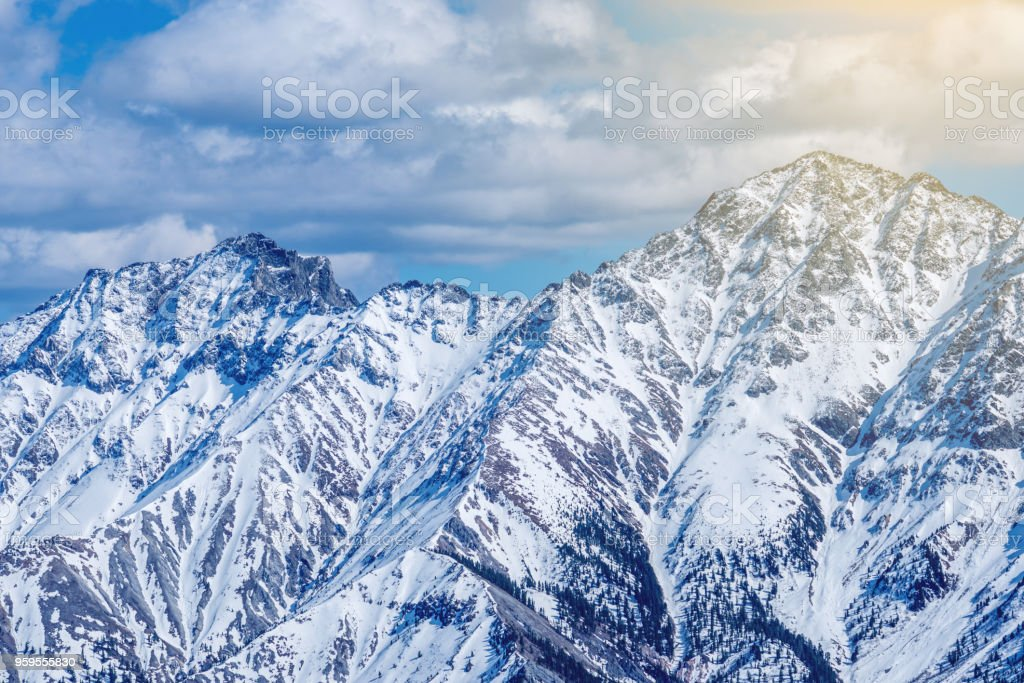 Landscape of snow-capped peaks of the rocky mountains in Sunny weather. Concept of nature and travel stock photo