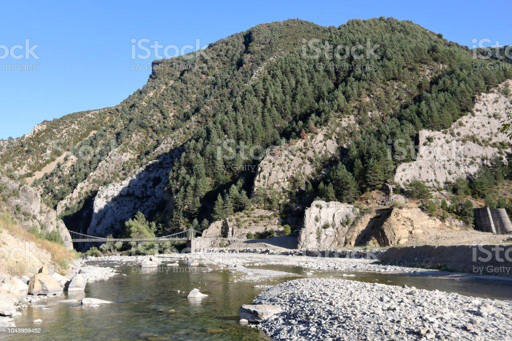 Un paisaje del Pirineo aragonés de español, con bosques, montañas y un viejo puente de madera que conduce a Janovas, un pueblo abandonado por la construcción de una presa. El río es el río Ara. - foto de stock