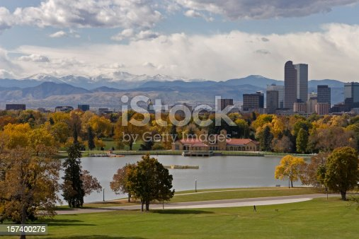 A person walks through Denver's city park with fall colors,downtown skyline and Mount Evans in the background, Colorado.