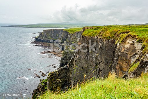 Landscape of the Irish countryside and rocky cliffs along the coastal walk route from Doolin to the Cliffs of Moher, geosites and geopark, Wild Atlantic Way, rainy day in county Clare in Ireland