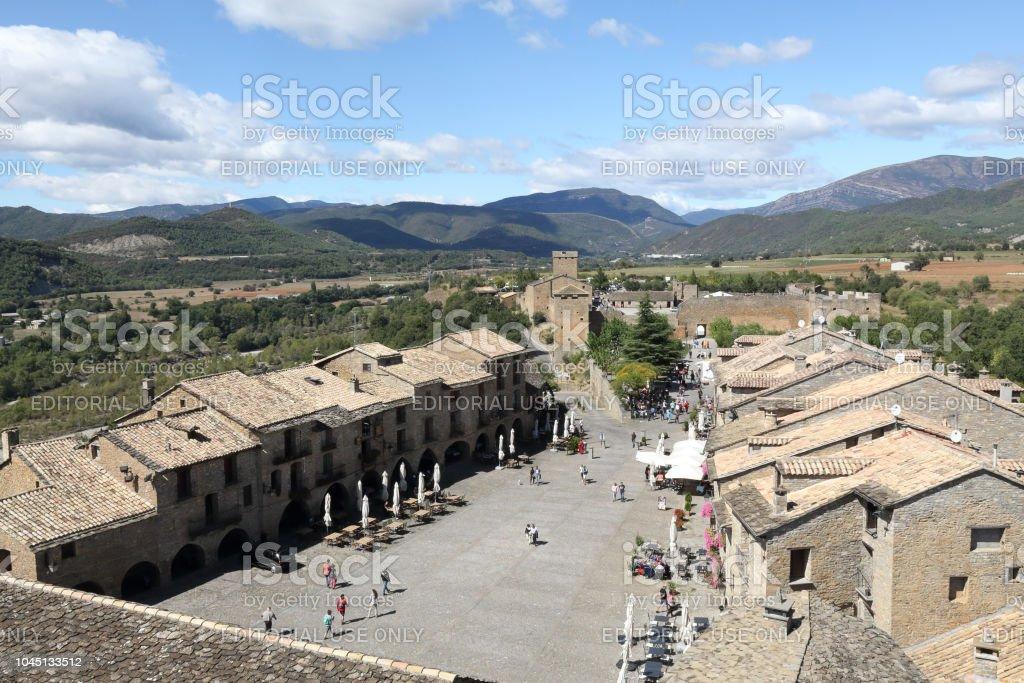 Un paisaje de la Plaza de armas (Plaza Mayor) rodeado de casas de piedra y rodeado de la vieja torre del castillo, con verdes montañas y un cielo azul como fondo, en Aínsa, un pueblo rural medieval en los Pirineos españoles - foto de stock