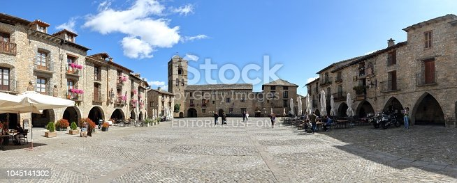 Ainsa, Spain - September 10, 2017: A landscape of the Main Square (Plaza Mayor) with the town hall at the bottom and some people shopping and chilling out in Ainsa, a small rural village in the Spanish Aragonese Pyrenees mountains