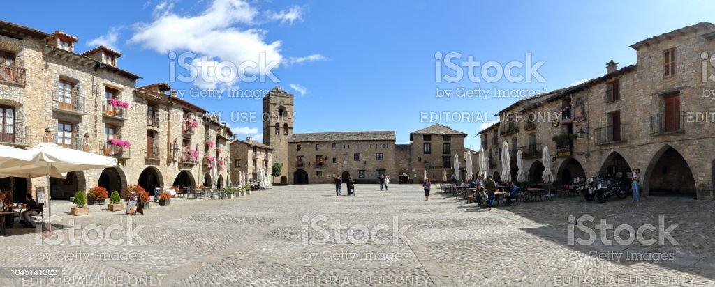 Un paisaje de la plaza principal (Plaza Mayor) con el Ayuntamiento en la parte inferior y algunas personas de compras y relajarse en Ainsa, un pequeño pueblo rural en las montañas del Pirineo Aragonés Español - foto de stock