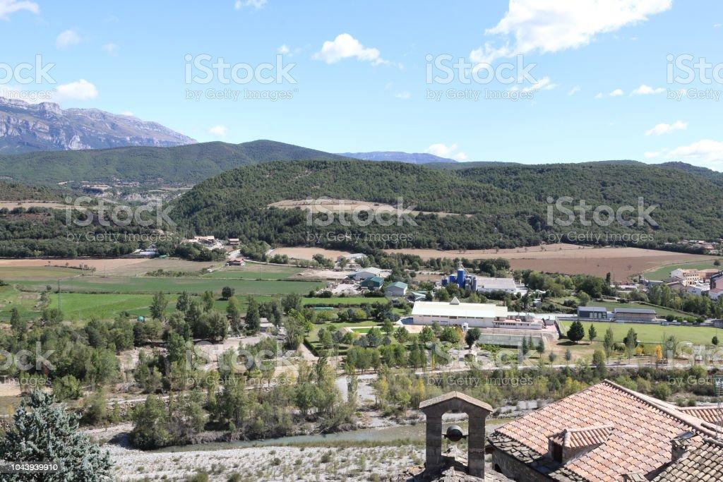 Un paisaje de los Pirineos con bosques verdes y un cielo azul con algunas nubes en la ciudad rural pequeña aragonés Ainsa, España - foto de stock
