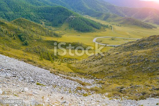 istock Landscape of the ridge covered with green trees and stones and view a valley flooded with sunlight, pasture, with dense clouds in the sky. Autumn day in the mountains of the Altai 1034391012