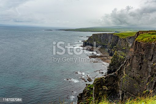 Landscape of the rocky cliffs in the Irish countryside along the coastal walk route from Doolin to the Cliffs of Moher, geosites and geopark, Wild Atlantic Way, rainy day in county Clare in Ireland