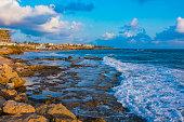 Landscape of the sundown in sea water amongst rocky beach the broken gangway