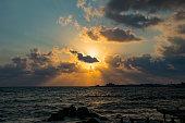 Landscape of the sundown in sea water amongst rocky beach