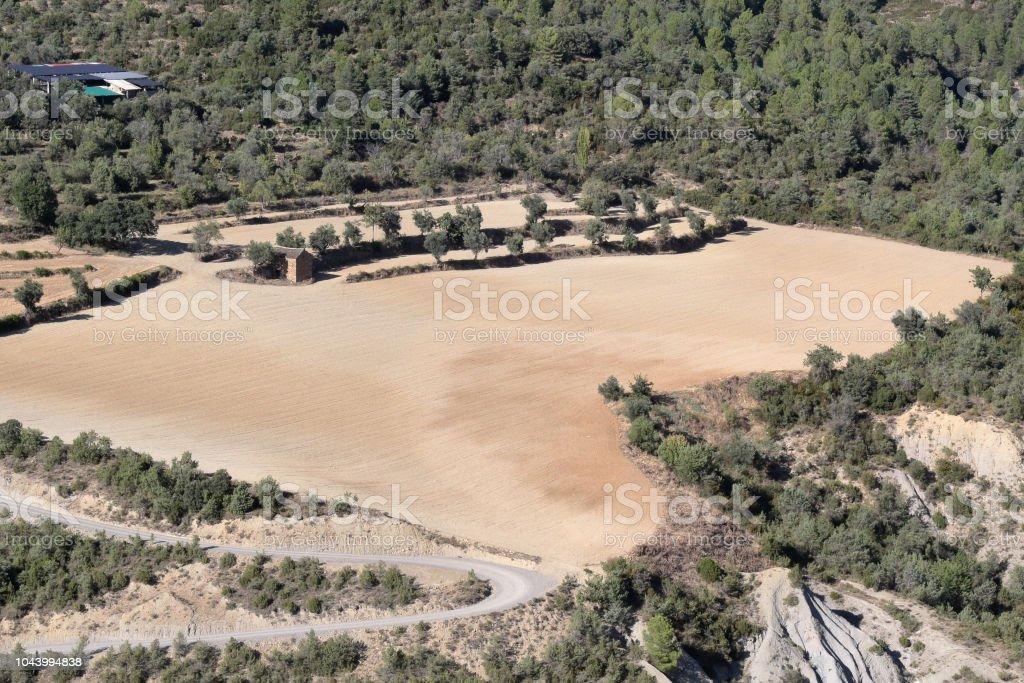 Un paisaje de campos amarillos cultivadores, arados para el cultivo, dentro de un denso bosque y montañas como se ve en el castillo del pueblo medieval rural de Boltaña, en el Pirineo Aragonés Español - foto de stock